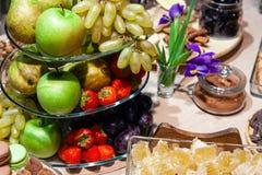 Fruits frais lumineux de plan rapproché : pommes, fraise, poire, raisin, cubes en nids d'abeilles dans le bol en verre, iris de f photographie stock