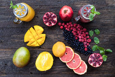 Fruits and frozen berries. On dark rustic wooden table. Purple and yellow smoothie bowl formula. Clean eating concept. Various green and red veggies, fruit and Royalty Free Stock Image