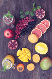 Fruits and frozen berries. On dark rustic wooden table. Purple and yellow smoothie bowl formula. Clean eating concept. Various green and red veggies, fruit and Royalty Free Stock Photography