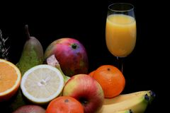 Fruits and fruit juice. Bananas, apple, oranges, and other fruits next to glass of fruit juice royalty free stock images