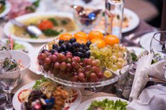 Fruits - Grapes, pears, tangerines. Against the background of the table with appetizers Stock Photo