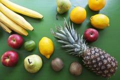 Fruits - group of objects. Pineapple, lemon, apple, avocado, orange, kiwi, bananas on the wood green background Stock Photography