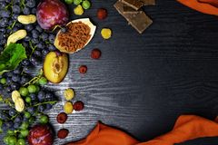 food rich with resveratrol, grapes, plums, goji, peanuts, cranberry,raspberrys chocolate on black wooden background stock images