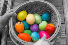 Fruits of the Hunt. Easter eggs in a basket held by a young girl Stock Photo
