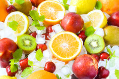 Fruits on ice. Colorful fruits, ice cubes and lemon balm leaves royalty free stock images