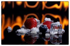 Fruits in Ice cubes over white at fire in backgraund and snow royalty free stock photos