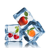 Fruits in ice cubes on the white royalty free stock image