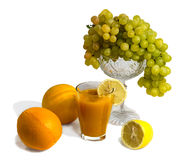 Fruits and juice isolated on white. Oranges, lemons, grapes and a glass of fruit juice Isolated on white Stock Photography