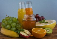 Fruits and juice. Various freshly squeezed fruits juices on wooden background Stock Photography