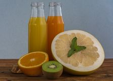 Fruits and juice. Various freshly squeezed fruits juices on wooden background Stock Images