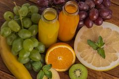Fruits and juice. Various freshly squeezed fruits juices on wooden background Royalty Free Stock Photos