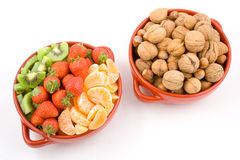 Fruits, kiwi, strawberry, mandarine and nuts, two bowls. Stock Images