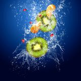 Fruits kokteil. Water drops around fruits on blue background royalty free stock photos