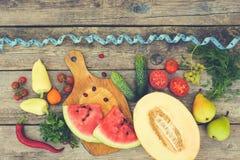 Fruits, légumes et dans la bande de mesure dans le régime sur le fond en bois Images libres de droits