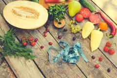 Fruits, légumes et dans la bande de mesure dans le régime sur le fond en bois Photos stock