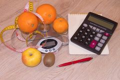 Fruits, Libra, calculator and centimeter on a wooden table. Diet concept Stock Photos