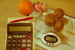 Fruits, Libra, calculator and centimeter on a wooden table. Diet concept Stock Photography