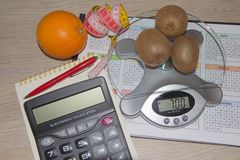 Fruits, Libra, calculator and centimeter on a wooden table. Diet concept. Fruits, Libra, calculator and centimeter on a wooden table. Low-calorie vegetables diet Stock Images