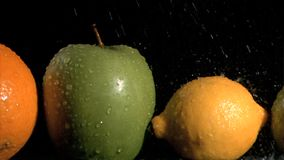 Fruits in line watered in super slow motion Stock Photo