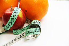 Fruits and measurement tape on the white background Royalty Free Stock Photography
