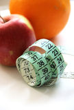Fruits and measurement tape on the white background Royalty Free Stock Images