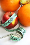 Fruits and measurement tape on the white background Royalty Free Stock Image