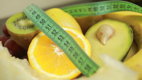 Fruits and measuring tape close up. The concept of diet stock video footage