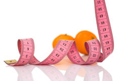 Fruits and measuring tape on a white background to symbolize diet. Orange fruits and measuring tape on a white background to symbolize a healthy diet stock photography