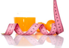Fruits and measuring tape on a white background to symbolize a healthy diet. Orange fruits and measuring tape on a white background to symbolize a healthy diet stock photos