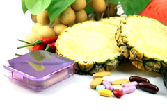 Fruits and medicines placed near the cosmetics. Fruits and medicines placed near the cosmetics on white background Royalty Free Stock Images