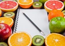 Fruits mix grapefruit orange apples with notebook Royalty Free Stock Photos