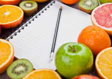 Fruits mix grapefruit orange apples with notebook Stock Images