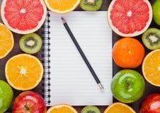 Fruits mix grapefruit orange apples with notebook Stock Image