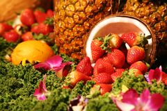 Fruits and More. Fruit arrangement with strawberries, lemons, greens and coconuts Royalty Free Stock Photos