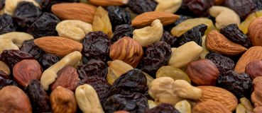 Fruits and nuts. Cashews, almonds, hazelnuts and raisins on a black background. Nuts and raisins are laid out in a large circle in the center of a large frame royalty free stock images
