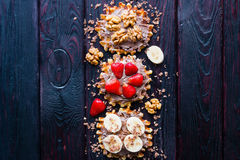 Fruits and nuts in the chocolate paste on waffle. On a black background Stock Photos