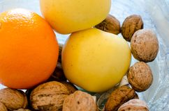 Fruits and nuts in glass bowl. Orange, yellow apples and nuts close up, fruits in glass bowl royalty free stock photos