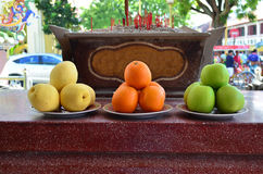 Fruits offering as a sacrifice at Chinese temple. Yellow pear, orange and green apple Stock Photos