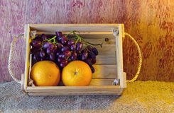 Fruits ( orange , grape )  in an wood box, on sack sisal background Royalty Free Stock Photography