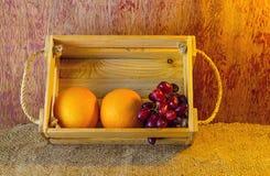 Fruits ( orange , grape )  in an wood box, on sack sisal background Stock Photo