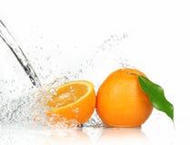 Fruits oranges avec éclabousser l'eau image stock