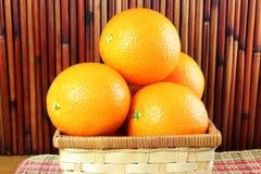 Fruits oranges mûrs frais dans le panier en bambou à l'arrière-plan en bambou Photo stock