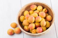 Fruits organiques mûrs d'abricots dans la cuvette en bois d'arbre de cendre image libre de droits