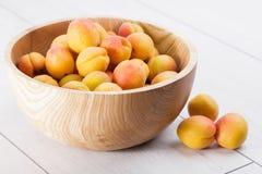 fruits organiques mûrs d'abricots dans la cuvette en bois d'arbre de cendre sur un fond en bois blanc images stock