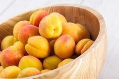 fruits organiques mûrs d'abricots dans la cuvette en bois d'arbre de cendre sur un fond en bois blanc image stock