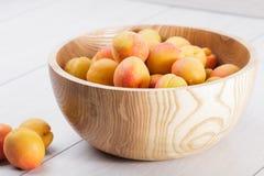 fruits organiques mûrs d'abricots dans la cuvette en bois d'arbre de cendre sur un fond en bois blanc photographie stock