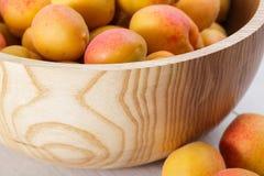 fruits organiques mûrs d'abricots dans la cuvette en bois d'arbre de cendre sur un fond en bois blanc images libres de droits