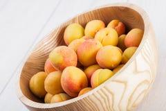fruits organiques mûrs d'abricots dans la cuvette en bois d'arbre de cendre sur un fond en bois blanc photo libre de droits