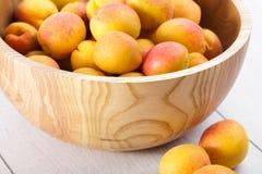 fruits organiques mûrs d'abricots dans la cuvette en bois d'arbre de cendre sur un fond en bois blanc photographie stock libre de droits