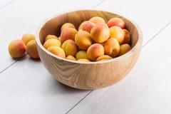 fruits organiques mûrs d'abricots dans la cuvette en bois d'arbre de cendre sur un fond en bois blanc photos libres de droits